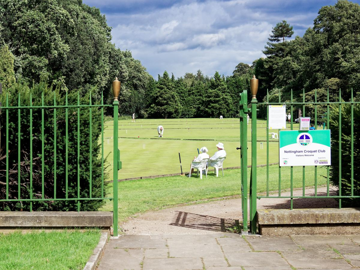 a view though small green wrought iron gates to the croquet lawns with people playing and others watching