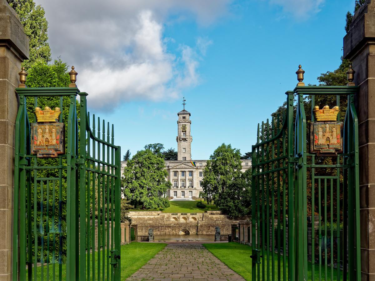 a pair of huge impressive wrought iron gates open with a vista to the grand Trent building