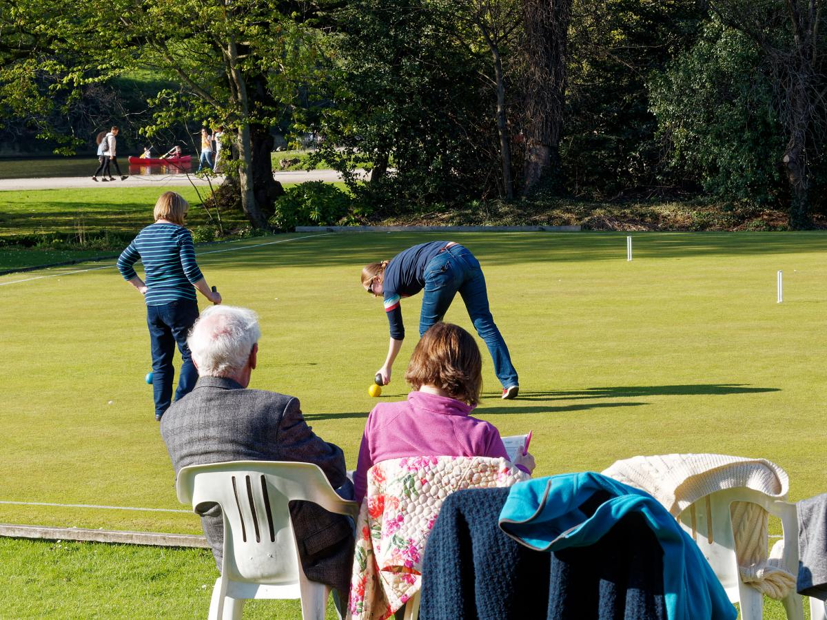 players and spectators in casual dress enjoying social croquet on a sunny afternoon